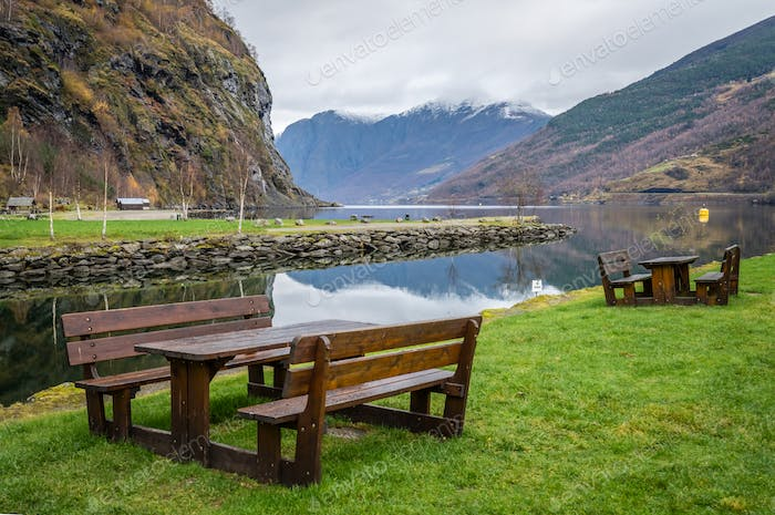 Wooden benches on a lawn in resting picnic area on the shore of