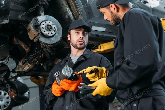 Automechaniker arbeiten mit Auto und Werkzeugen in der Werkstatt