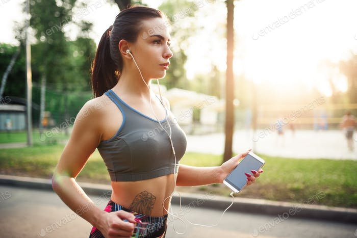 Athletic girl jogging with headphones in park