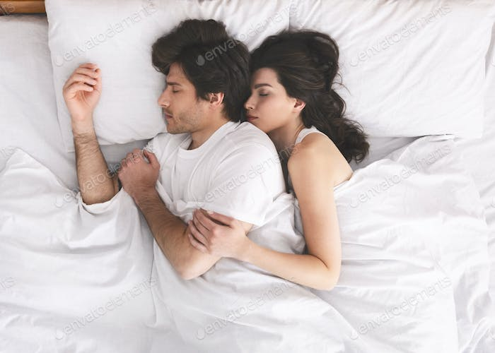 Millennial married couple cuddling, sleeping closely in bed