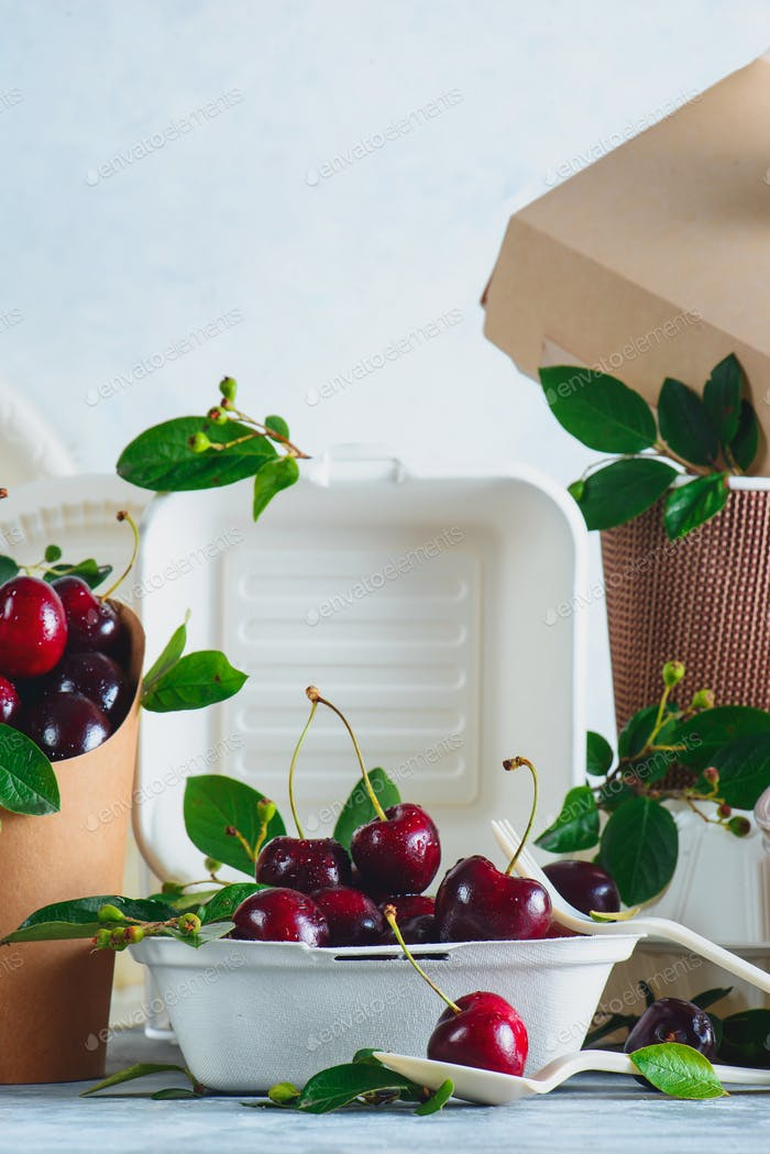 Eco-friendly food packaging with cherries. White containers, plates and other catering disposables