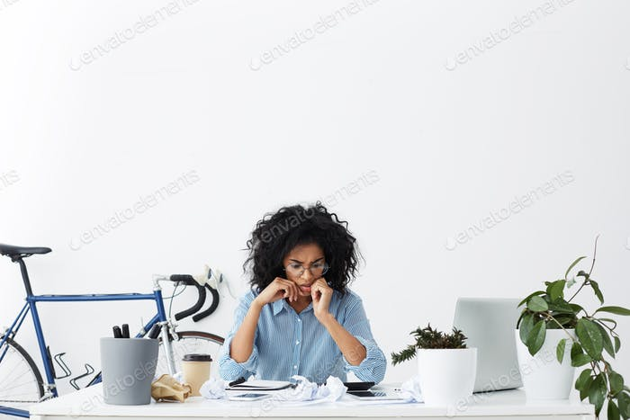 Worried young female office worker with curly hair having anxious desperate look while facing deadli