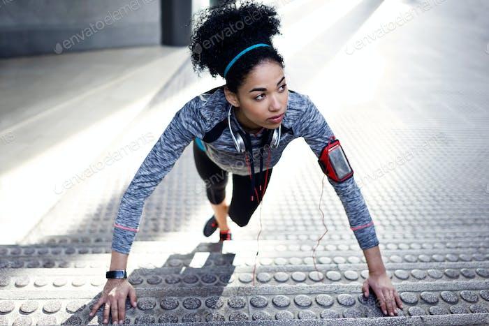 Fit und sportliche junge Frau tun Stretching in der Stadt.