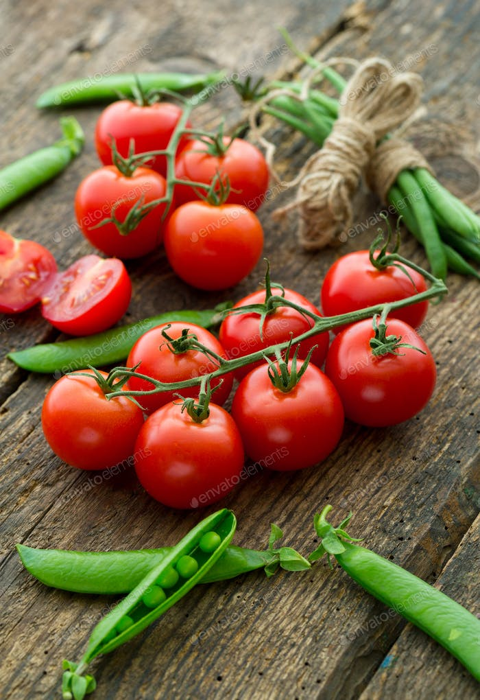 Fresh tomatoes with asparagus and green peas on a wooden backgro