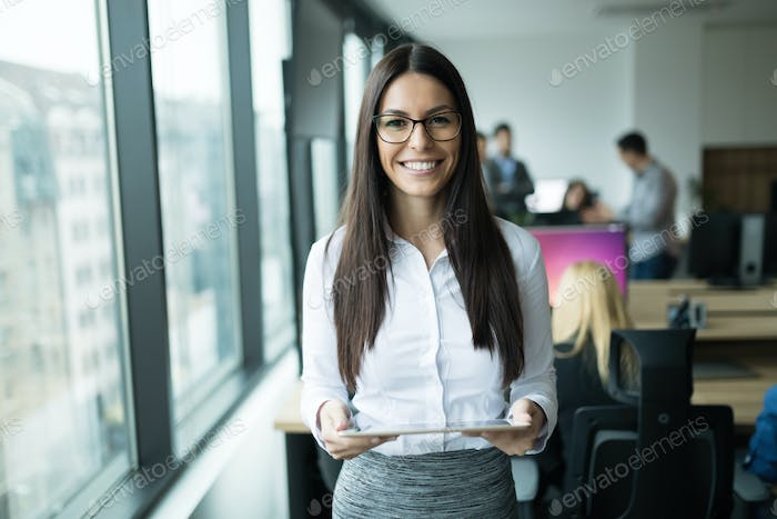 Beautiful cheerful businesswoman holding tablet