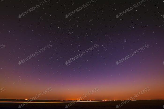 Night Starry Sky Over Yellow Sunset Or Sunrise Lights. Night Glo