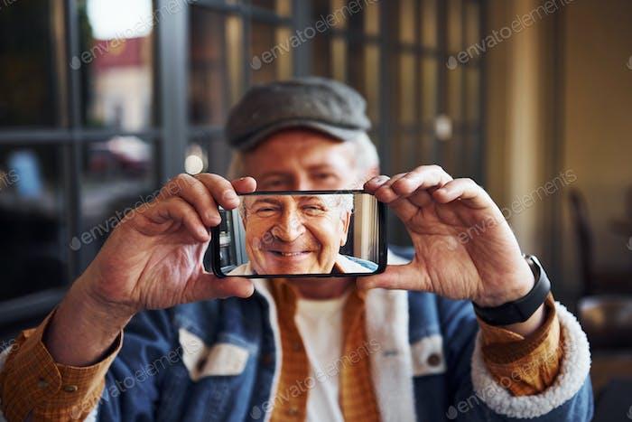 Stilvolle Senior in modischer Kleidung und in Brille sitzt im Café und hält Telefon