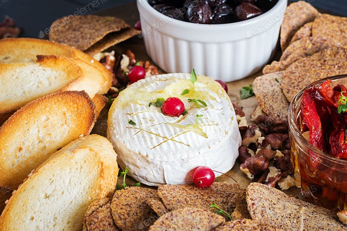 Traditional french baked camembert cheese with thyme and toast, walnuts, olives