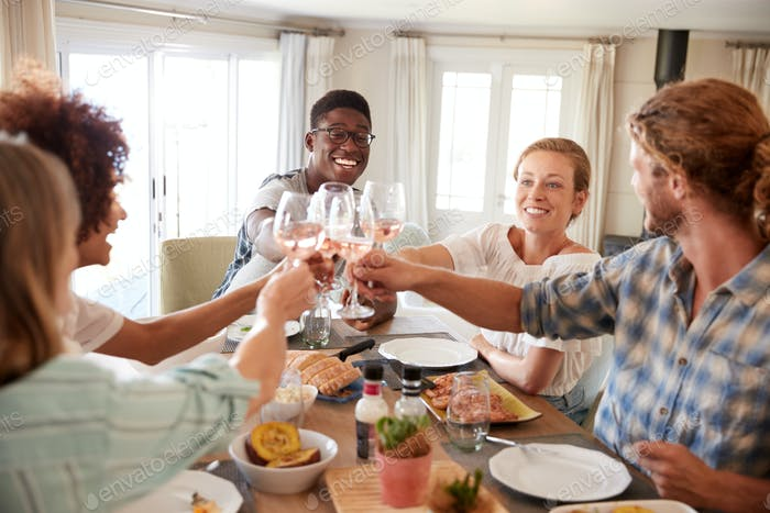 Millennial friends sitting at a dining table making a toast during lunch, close up