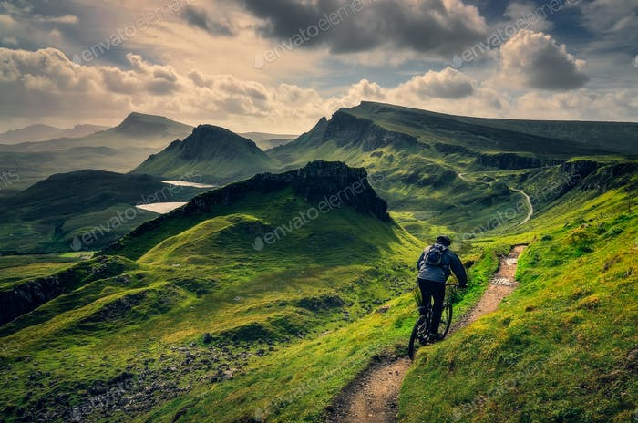 Mountain biker riding through rough mountain landscape of Quiraing, Scotland