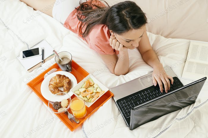 Женщина наблюдает за ноутбуком и завтракает