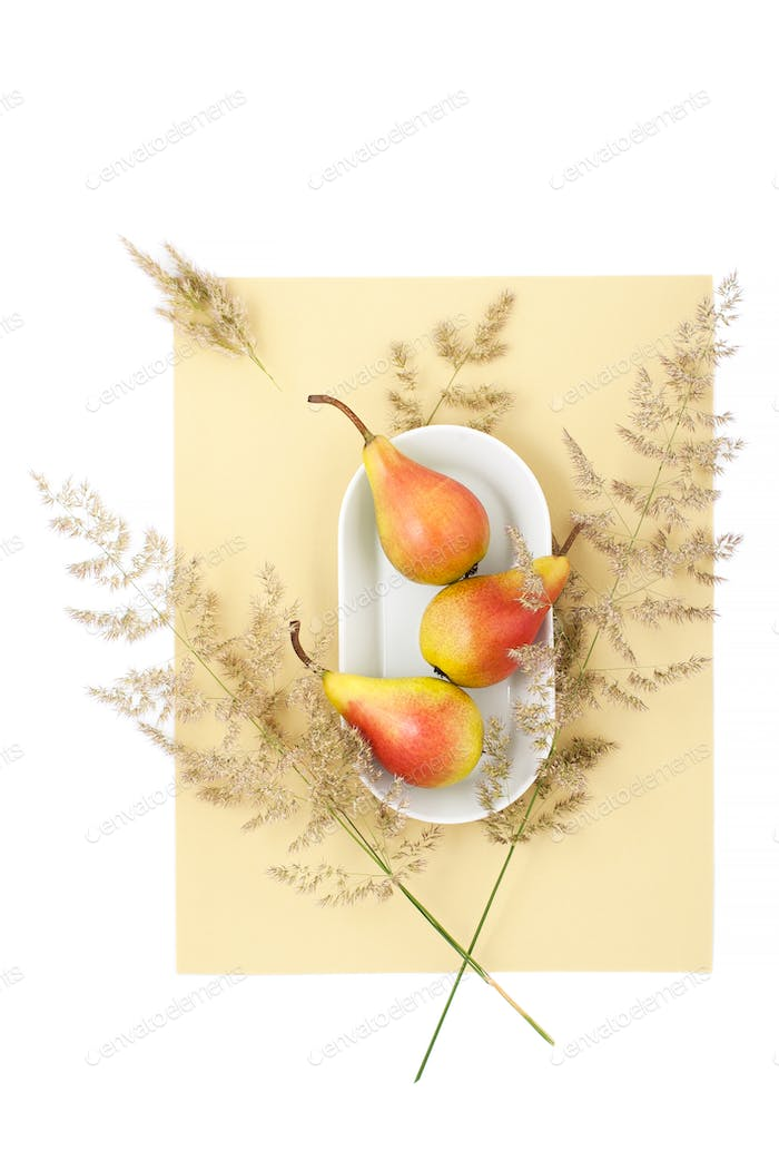 Three ripe pears on a white plate on a light white-yellow pastel