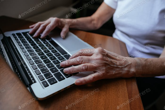 Close up of old woman hands writing on laptop.