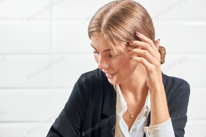 Elegant lady in office suit satisfied after manicure procedure in salon
