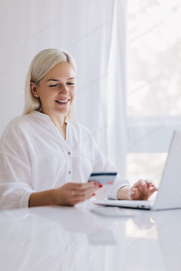 Woman paying with her credit card for online shopping.