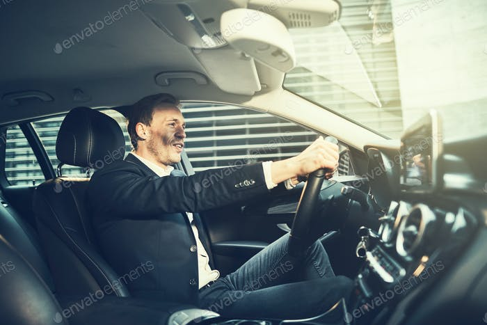 Smiling businessman driving his car through the city streets