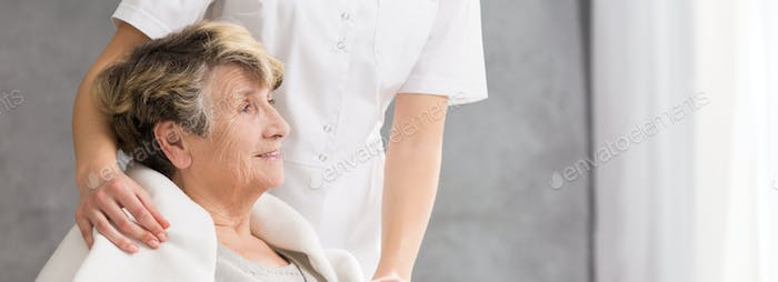 Nurse standing behind senior woman