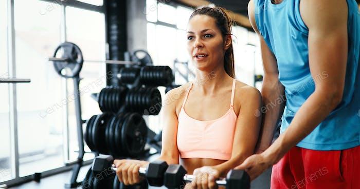 Personal Trainer hilft fit Frau im Fitnessstudio