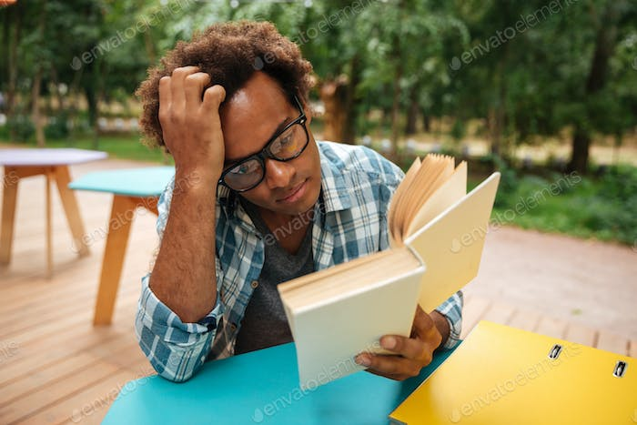 Thoughtful african young man reading book outdoors