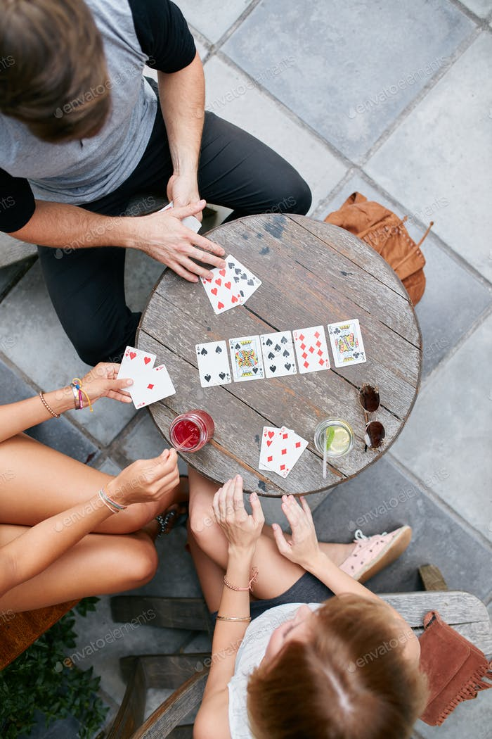 Young friends playing poker card game at cafe
