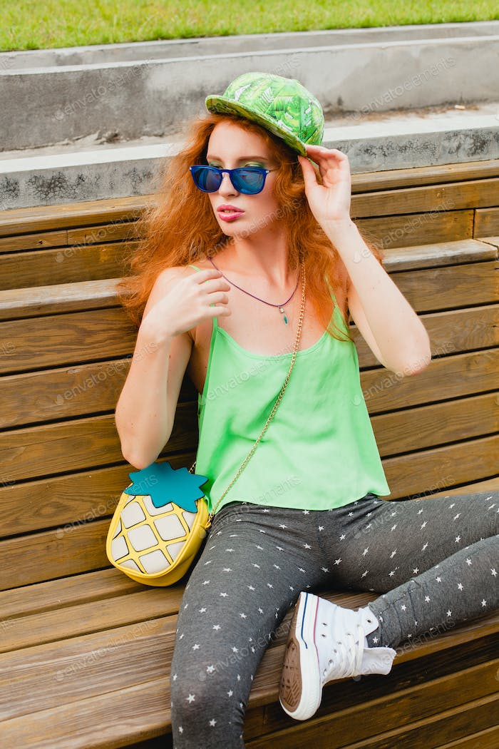 young stylish hipster ginger woman, sitting on bench