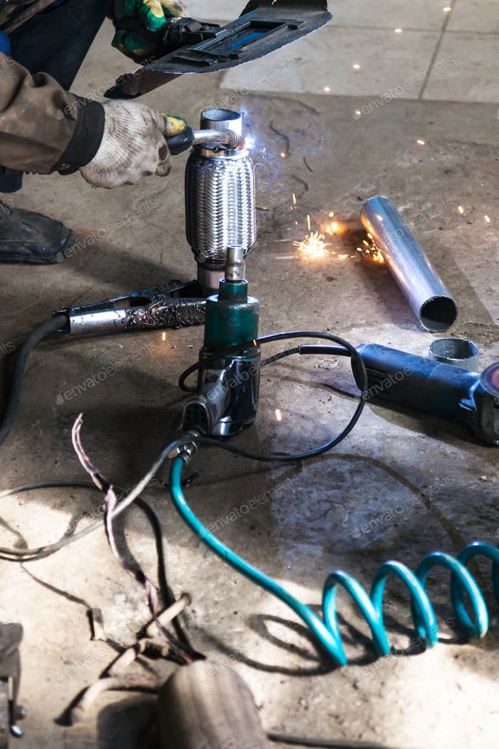 welder fixes pipe on corrugation muffler
