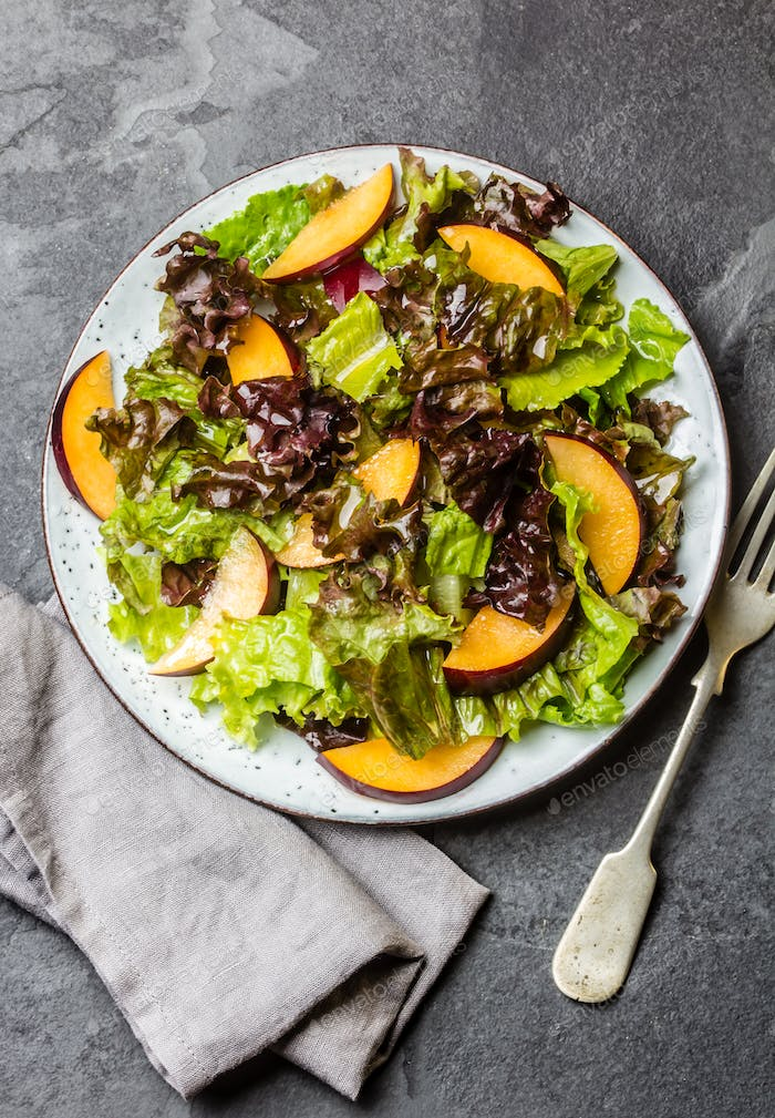 Lettuce salad with plums, slate background.