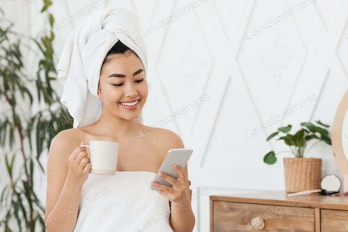 Happy asian woman drinking coffee and using mobile phone