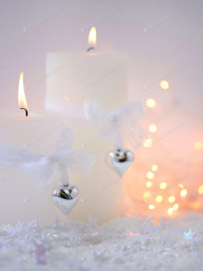 Weihnachtskerzen auf dem Schnee und Weihnachtsbeleuchtung. Festliche Chri