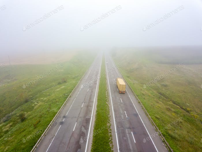 Aerial view from the drone a misty morning on the road with a truck around the field