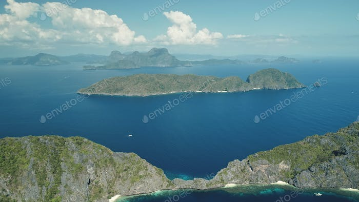 Hill island at sea bay aerial shot. Landscape of green forest trees mountain isles atserene seascape