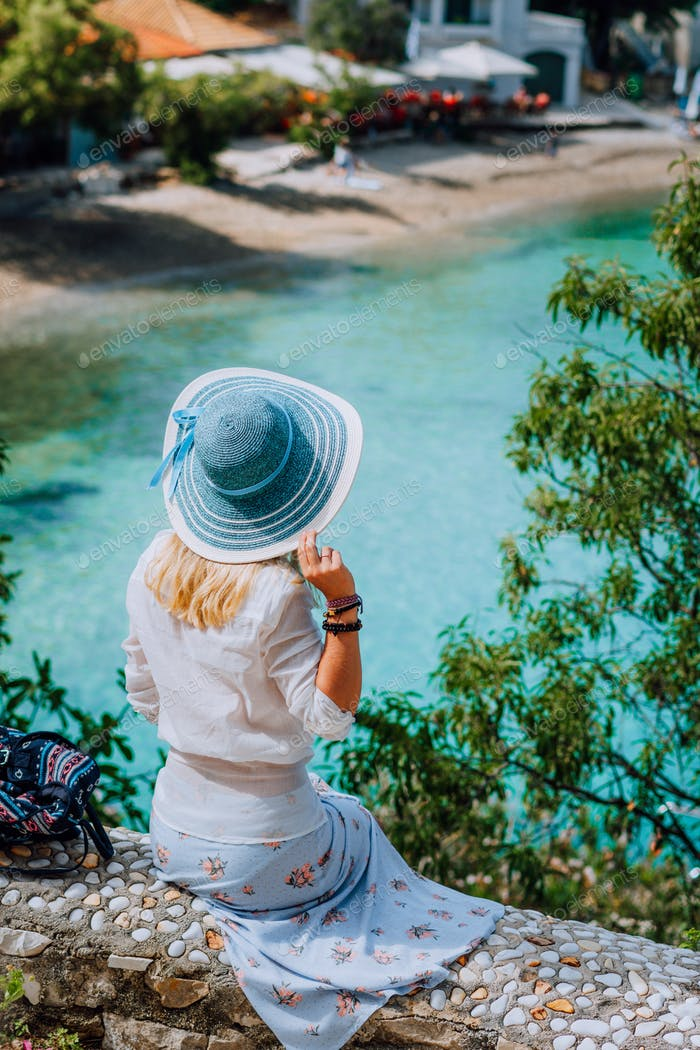 Blond beautiful woman with blue sunhat and white clothes sitting in front of blue bay of colorful