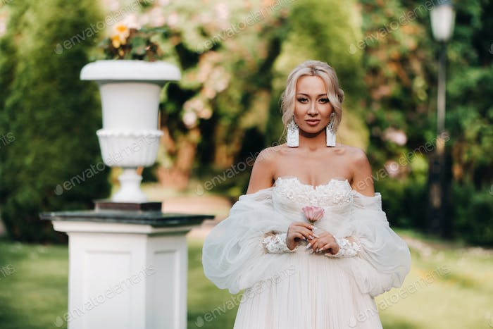 Beautiful bride in a luxurious wedding dress holds a bouquet of white roses and greens on a green