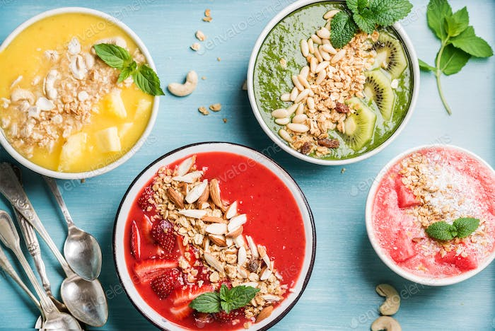 Healthy summer breakfast concept. Colorful fruit smoothie bowls on turquoise blue background