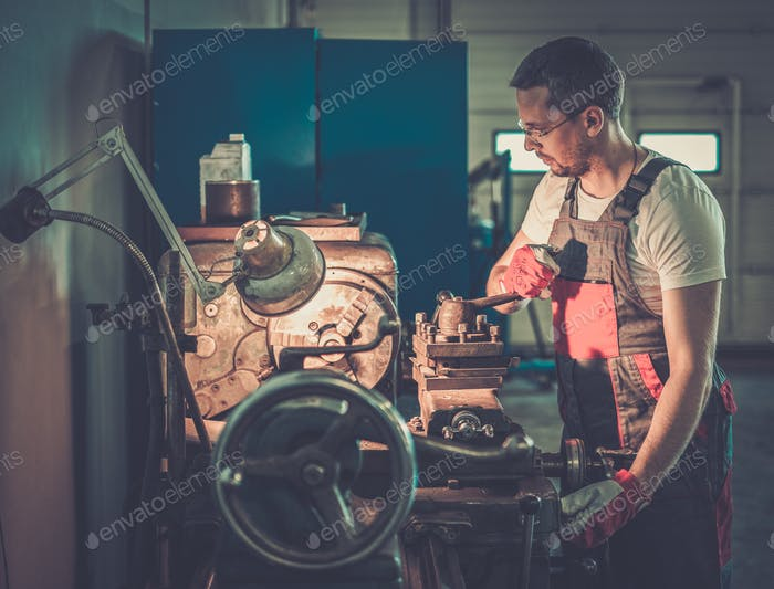 Serviceman working on lathe machine in car workshop