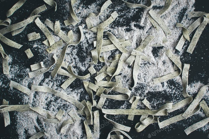 Pasta tagliatelle covered by flour on a black background