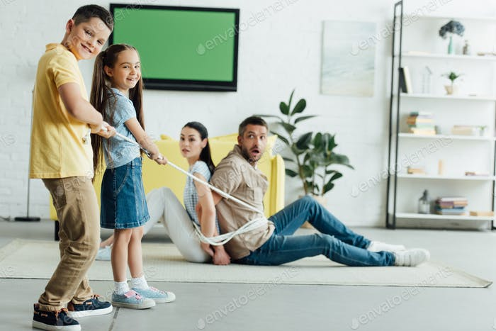 happy kids tying parents with rope on floor at home