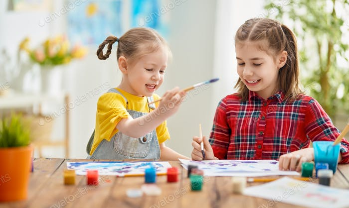 Happy kids are painting at home.