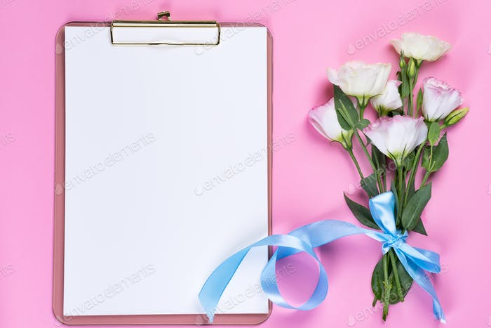 Minimal composition with a Eustoma flowers in an envelope with clipboard on a pink background, top