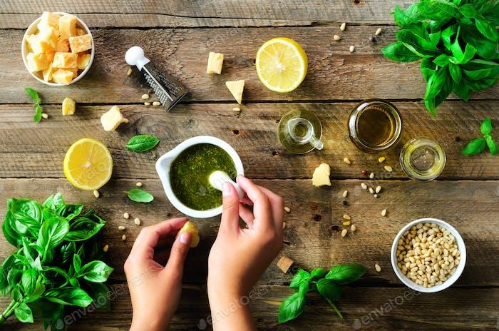 Woman hands making italian pesto in bowl. Ingredients - basil, lemon, parmesan, pine nuts, garlic