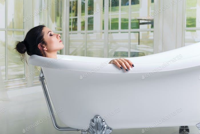 Bathing woman relaxing in bath smiling relaxing with eyes closed.