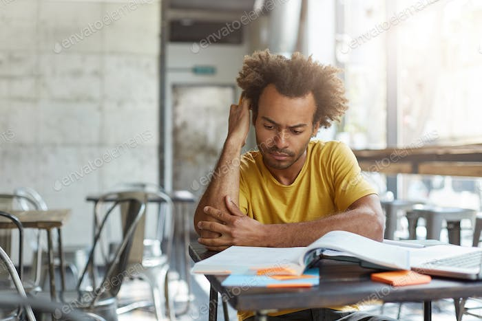 People, lifestyle and education. Focused attractive Afro American university student studying at mod