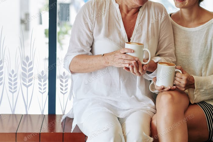 Mother and daughter with coffee mugs
