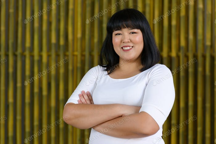 Young beautiful overweight Asian woman outdoors