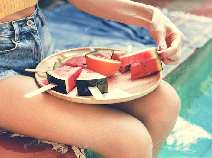 Caucasian woman eating watermelon in summertime