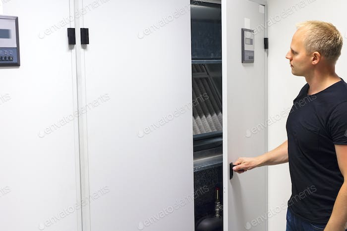 Technician Opening Air Conditioner Cabinet In Datacenter