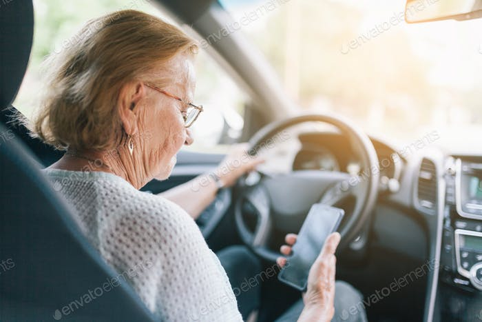 Elderly woman behind the steering wheel using her phone
