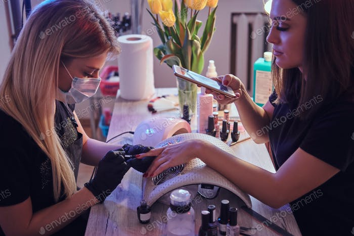 Woman takes a photograph of the manicure procedure in the beauty salon