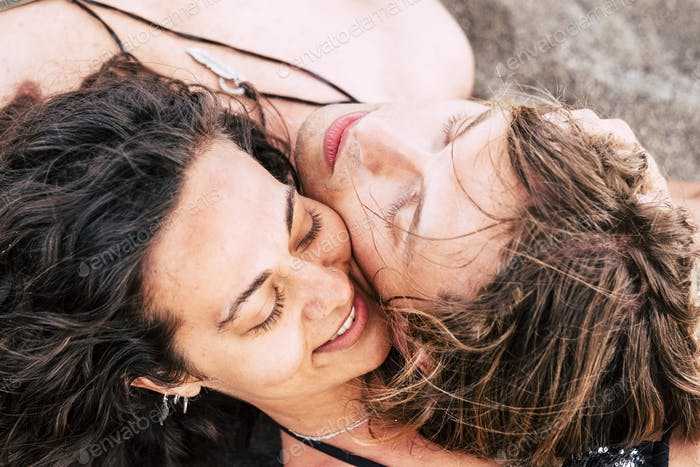 beautiful young couple of caucasian models man and woman lay down together