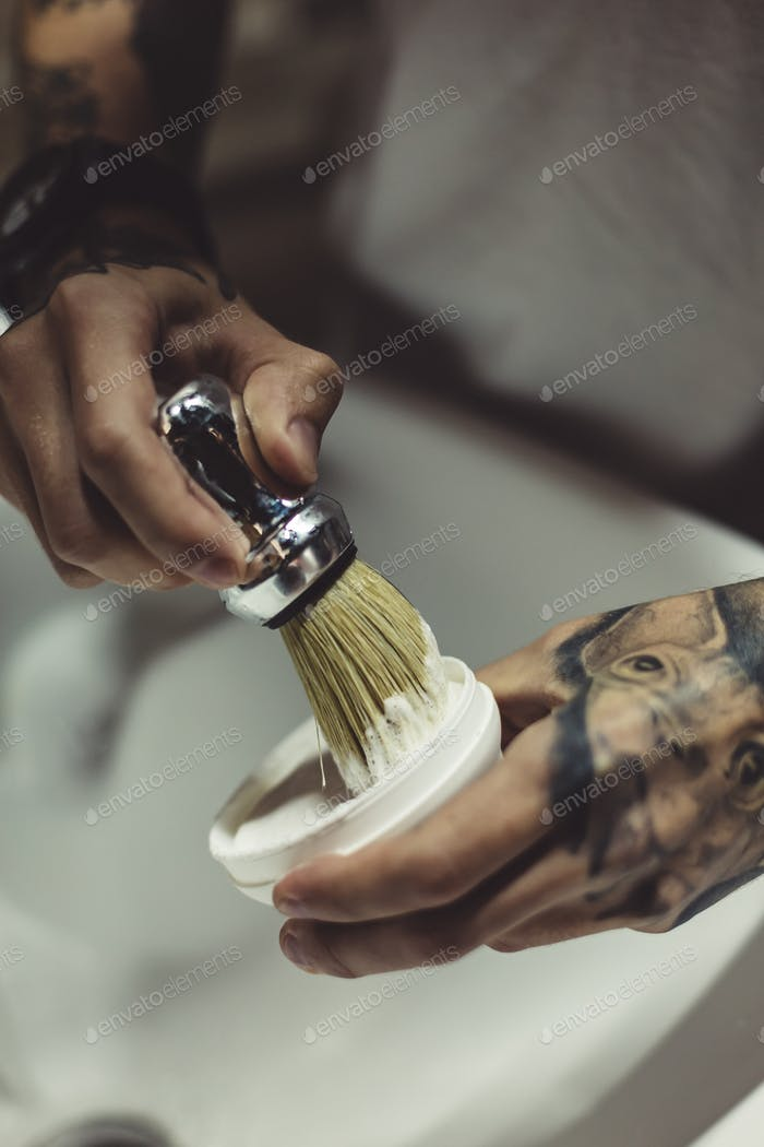 Crop tattooed barber making foam